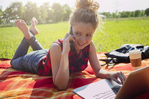 Woman lying on blanket on a meadow telephoning with smartphone - GIOF001154