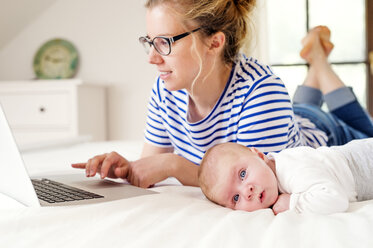 Mother with baby lying on bed working with laptop - HAPF000454