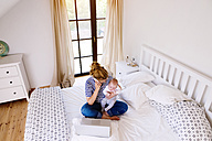 Mother with baby at home working with laptop - HAPF000457