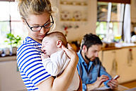 Mother holding little baby with father in background - HAPF000463