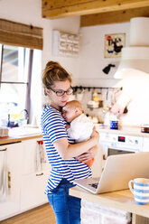 Mother with baby in kitchen looking at laptop - HAPF000466