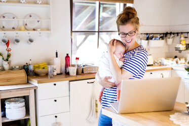 Happy mother with baby in kitchen looking at laptop - HAPF000469
