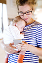 Mother holding little baby looking at cell phone - HAPF000472