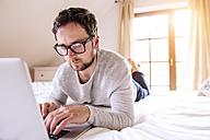 Man lying on bed using laptop - HAPF000481