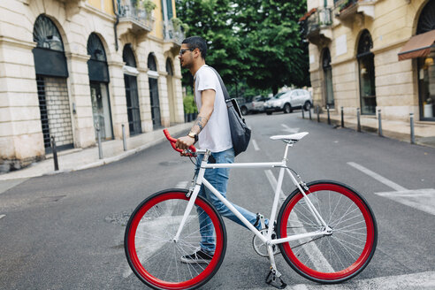 Young man walking with a bicycle in the city - GIOF001165