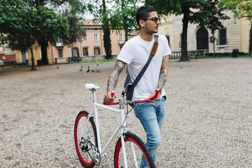 Young man walking with a bicycle in the city - GIOF001168