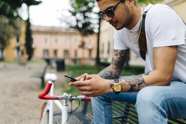 Young man sitting on bench looking at cell phone - GIOF001171