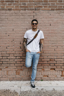 Smiling young man leaning against a brick wall - GIOF001174