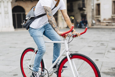 Young man riding bicycle in the city - GIOF001177