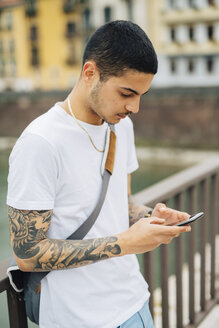 Young man outdoors looking at cell phone - GIOF001180