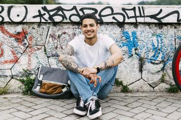 Smiling young man sitting at graffiti wall - GIOF001183