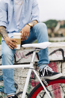 Young man with a bicycle and coffee to go sitting on graffiti wall - GIOF001186