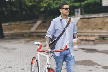 Young man walking with a bicycle in the city - GIOF001189