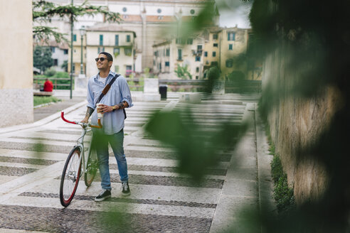 Young man walking with a bicycle in the city - GIOF001192