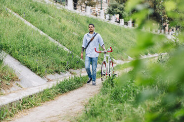 Young man walking with a bicycle on a path - GIOF001198