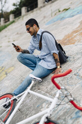 Young man with a bicycle sitting on a wall looking at cell phone - GIOF001201