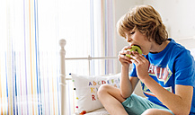 Portrait of boy sitting on the couch eating an apple - MGOF001898