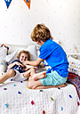 Boy tickling his little brother on the couch - MGOF001904