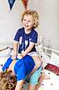 Portrait of little boy riding on his older brother at home - MGOF001907