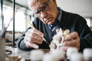 Senior man decorating ceramic in his spare time - JRFF000698
