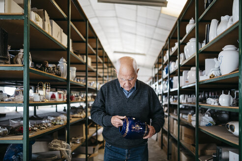 Elderly man reviewing the ceramic piece - JRFF000704
