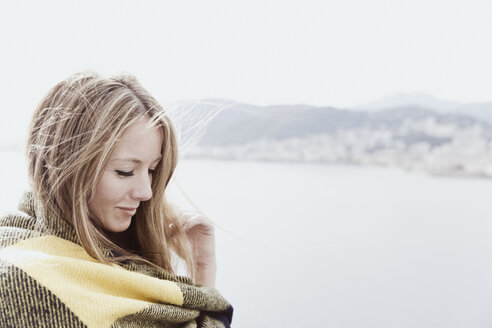 Portrait of blond woman covered with blanket on deck of a cruise liner - ONBF000035