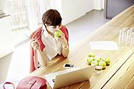 Woman in a modern canteen eating an apple - TSFF000022