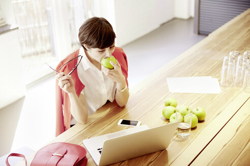 Woman in a modern canteen eating an apple - TSFF000022