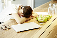 Woman napping at table in canteen of a modern office - TSFF000025