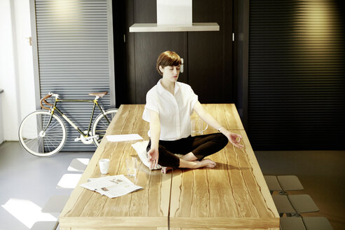 Woman practising yoga on wooden table - TSFF000028