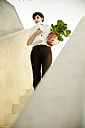 Woman with folder and potted plant standing on staircase - TSFF000031
