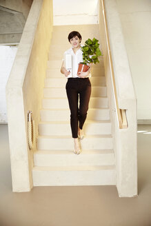 Woman with folder and potted plant standing on staircase - TSFF000034