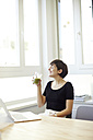 Happy woman drinking green smoothie in the office - TSFF000043