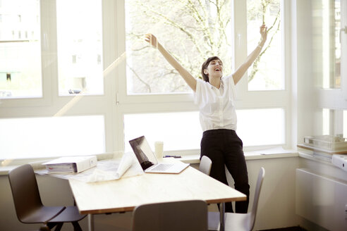 Laughing woman doing stretching exercise in her office - TSFF000049