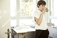 Woman drinking glass of green smoothie in an office - TSFF000052