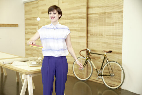Portrait of smiling woman playing with table tennis racket and ball in the office - TSFF000076