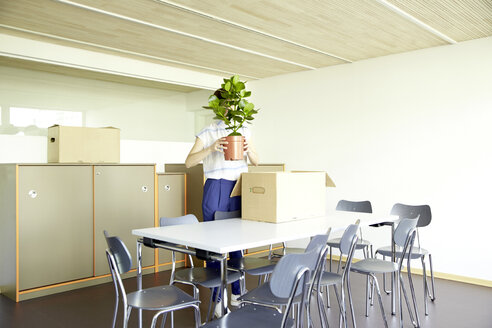 Woman hiding behind potted plant in new office - TSFF000079
