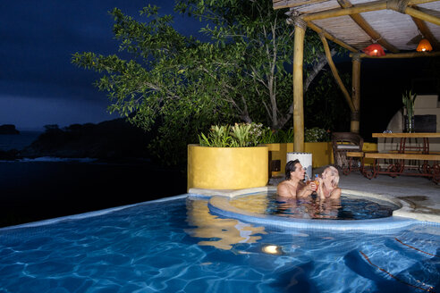 Couple enjoying cocktails in swimming pool at night - ABAF002025