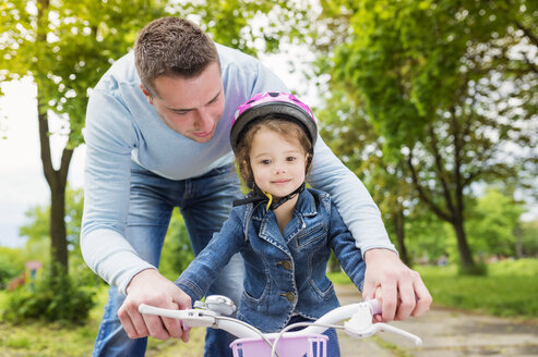 Father accompanying daughter on bike - HAPF000484