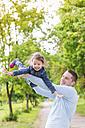 Father playing with daughter in park - HAPF000496