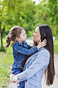 Mother holding daughter in park - HAPF000499
