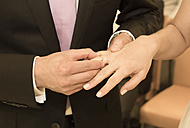 Groom putting wedding ring on bride's hand - FCF000969