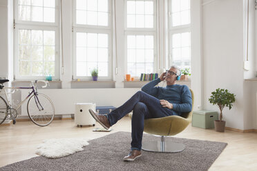 Relaxed mature man at home sitting in chair listening to music - RBF004537