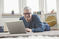 Mature man at home lying on floor using laptop - RBF004543
