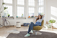 Relaxed woman at home sitting in chair - RBF004552