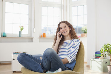 Woman at home sitting in chair talking on cell phone - RBF004558