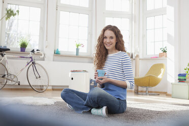 Smiling woman at home sitting on floor - RBF004561