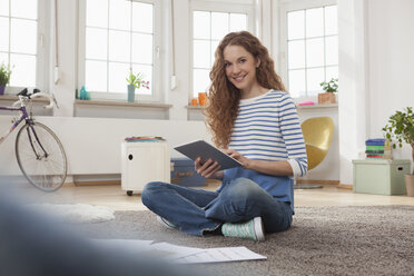 Woman at home sitting on floor using digital tablet - RBF004564