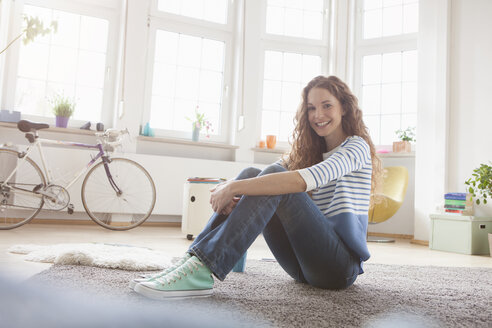 Smiling woman at home sitting on floor - RBF004567