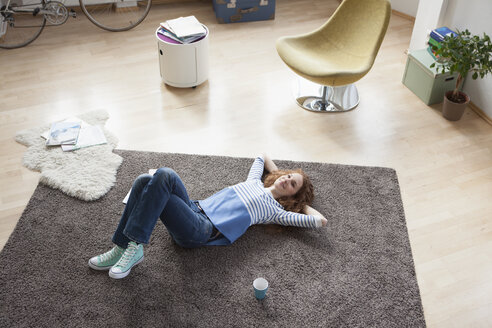 Relaxed woman at home lying on floor - RBF004573